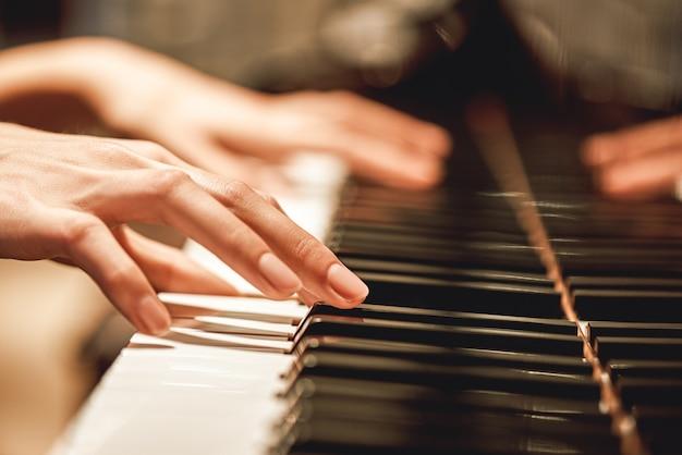 Piękna melodia fortepianuzbliżenie widoku kobiecych rąk grających na pianinie w jej ulubionej muzyce klasycznej