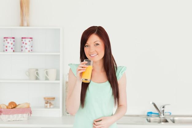 Piękna miedzianowłosa kobieta cieszy się szkło sok pomarańczowy w kuchni