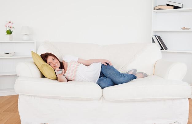 Piękna miedzianowłosa kobieta ogląda tv podczas gdy kłamający na kanapie