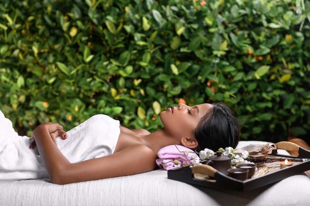 Piękna międzyrasowa dziewczyna leży na stole do masażu, na którym stoi taca z aromatycznymi olejkami