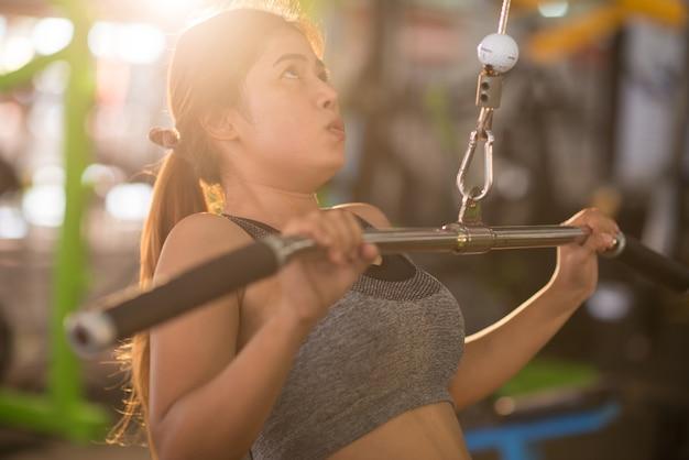 Piękna mięśniowa dysponowana kobieta ćwiczy budynków mięśnie w th gym