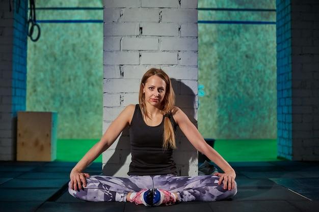 Piękna mięśniowa dziewczyna w szarych legginsach robi rozciąganiu. hala sportowa w stylu industrialnym