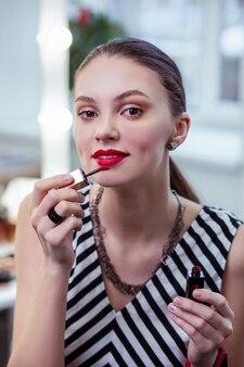 Piękna miła kobieta będąca w dobrym nastroju podczas nakładania szminki