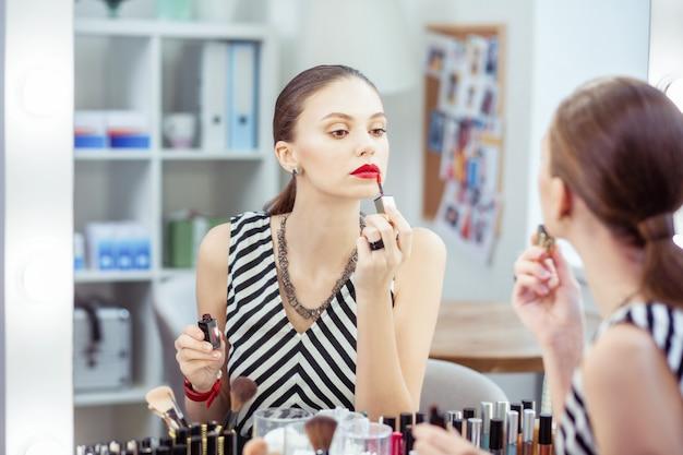 Piękna miła młoda kobieta nakłada szminkę stojąc przed lustrem