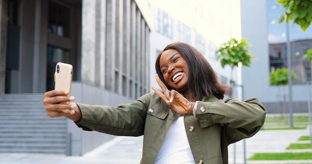 Piękna młoda african american kobieta pozowanie i uśmiecha się do aparatu smartfona podczas robienia zdjęć selfie na ulicy. dość wesoła stylowa kobieta robi zdjęcia selfie z telefonu komórkowego.