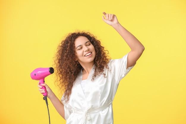 Piękna młoda afroamerykańska kobieta z suszarką na kolorowym tle