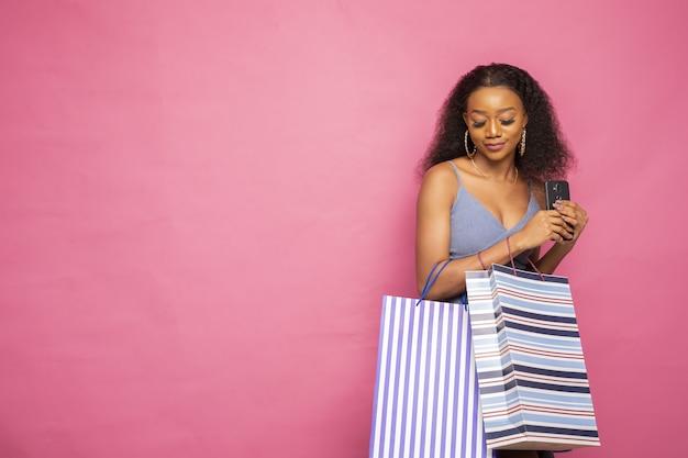 Piękna młoda afrykańska dziewczyna trzyma torby na zakupy i telefon komórkowy