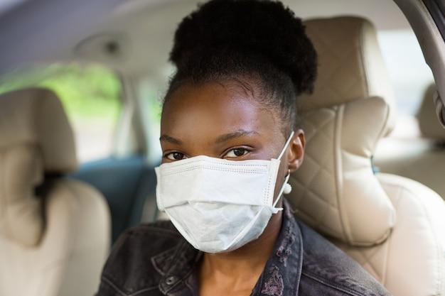 Piękna młoda afrykańska kobieta jazdy samochodem w masce medycznej