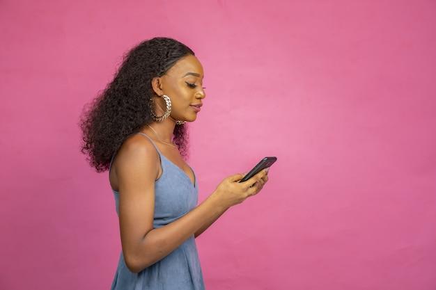 Piękna młoda afrykańska kobieta korzystająca ze swojego telefonu komórkowego