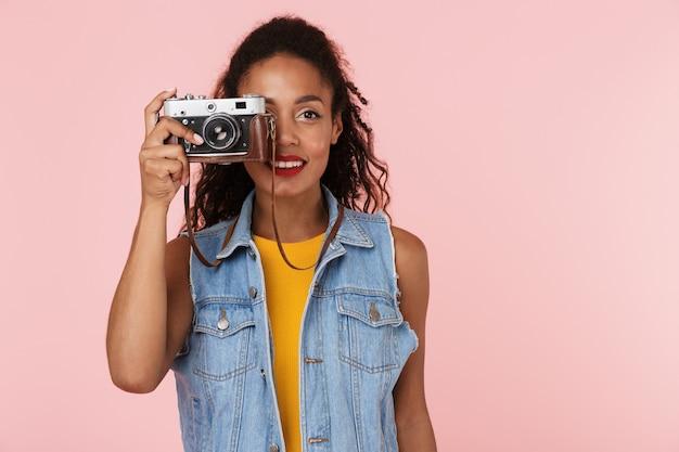 Piękna młoda afrykańska kobieta na białym tle nad różową ścianą trzymając aparat