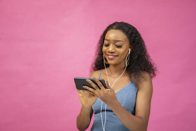 Piękna młoda afrykańska kobieta ogląda wideo przy użyciu swojego telefonu, mając na sobie parę słuchawek