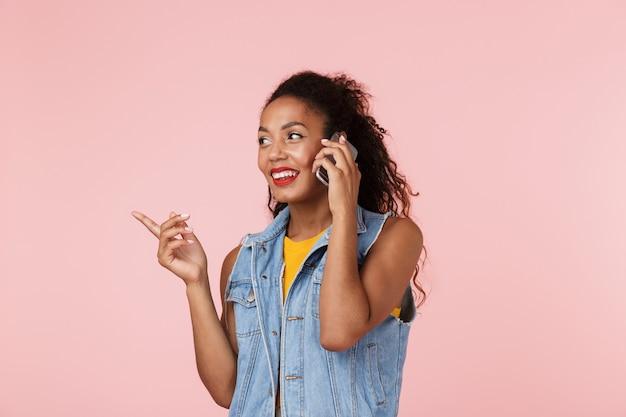 Piękna młoda afrykańska kobieta rozmawia przez telefon, wskazując