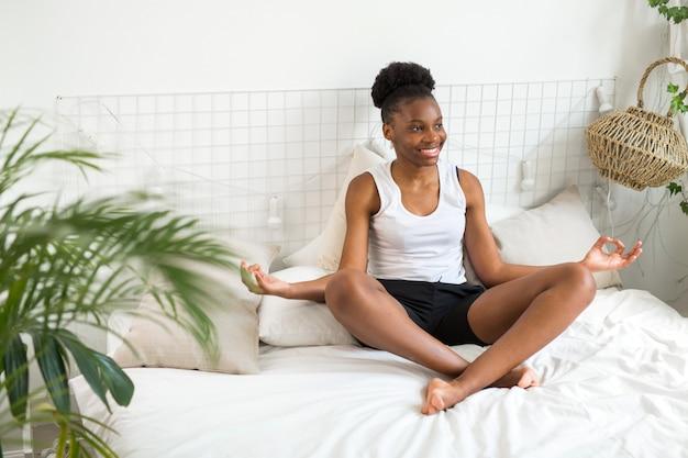 Piękna młoda afrykańska kobieta siedzi na łóżku w pozie jogi