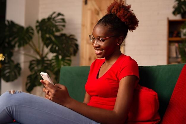 Piękna młoda afrykańska kobieta siedzi z telefonem komórkowym na kanapie