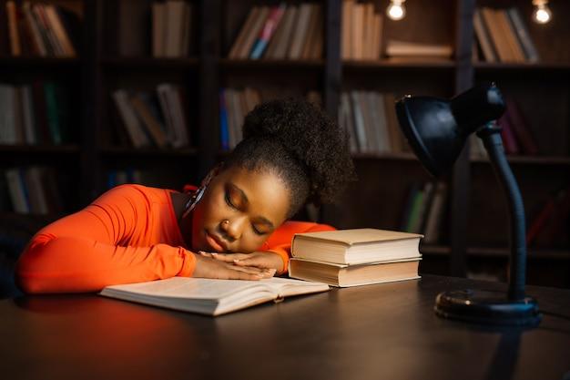 Piękna młoda afrykańska kobieta śpi przy stole z książkami