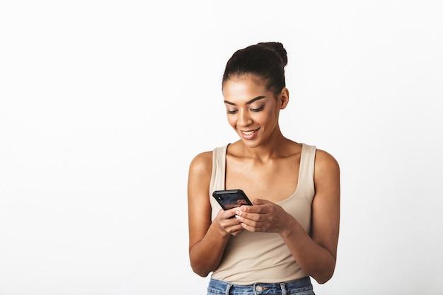 Piękna młoda afrykańska kobieta ubrana niedbale stojąc na białym tle, przy użyciu telefonu komórkowego