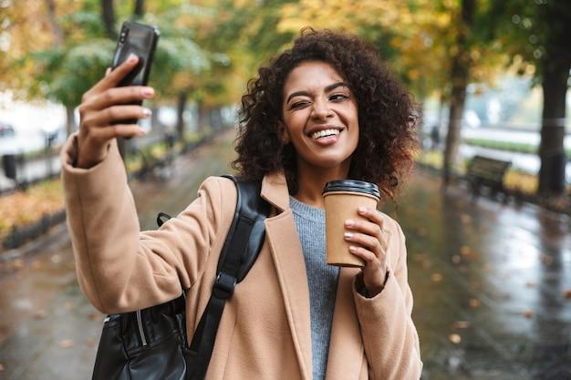 Piękna młoda afrykańska kobieta ubrana w płaszcz spaceru na świeżym powietrzu w parku, niosąc plecak, biorąc selfie