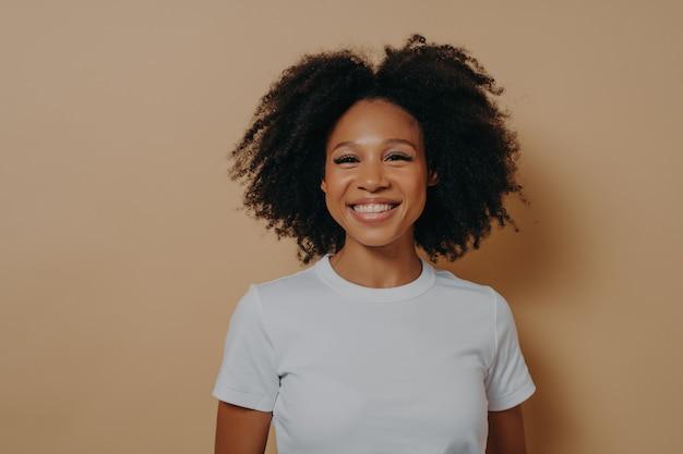 Piękna młoda afrykańska kobieta uśmiecha się radośnie do kamery i demonstruje szczęście, stojąc przed kolorową ścianą w studio, ciemnoskóra kobieta w swobodnym stroju z kręconymi włosami pokazującymi białe zęby
