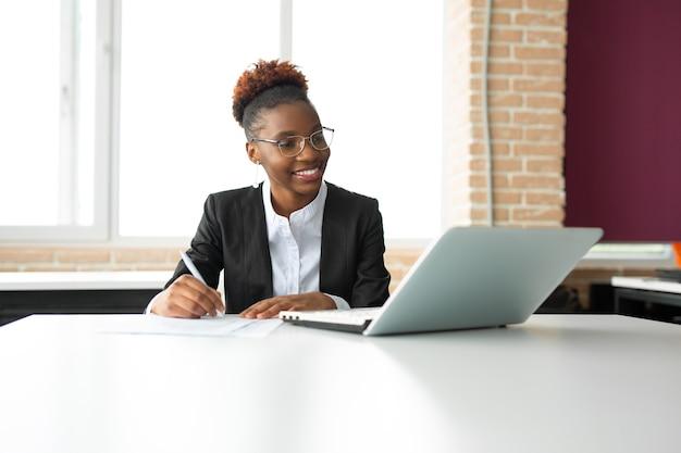 Piękna młoda afrykańska kobieta w okularach z laptopem