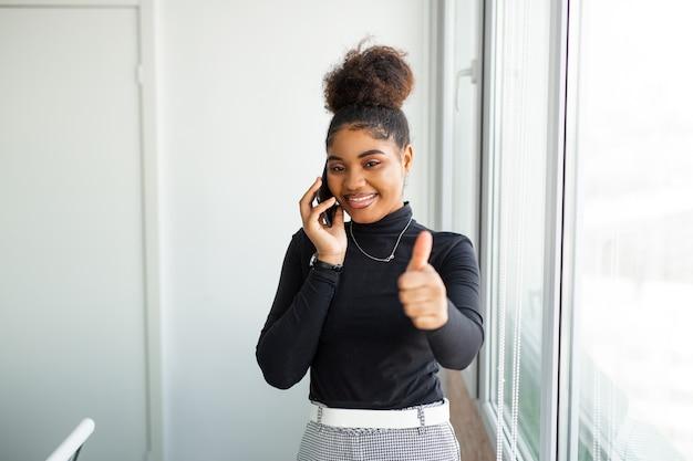 Piękna młoda afrykańska kobieta z telefonem komórkowym z gestem ręki