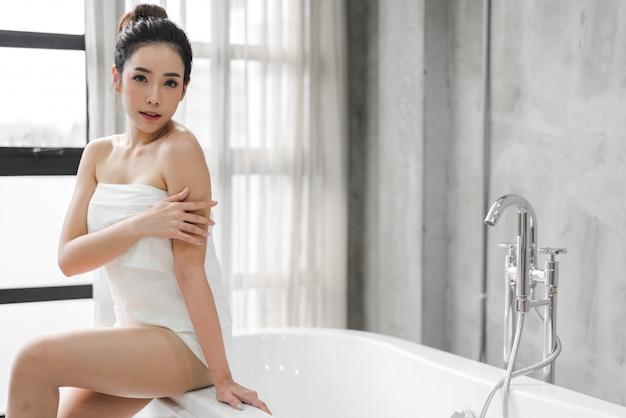 Piękna młoda asia kobieta cieszy się relaksować brać skąpanie na wannie przy łazienką