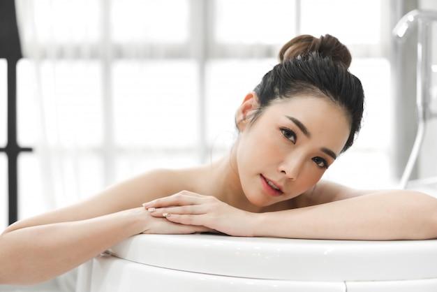 Piękna młoda asia kobieta cieszy się relaksować brać skąpanie z bąbel pianą w wannie przy łazienką