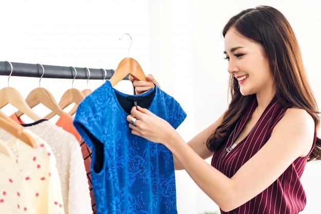 Piękna młoda asia kobieta robi zakupy i wybiera odziewa w sklepie moda zakupy pojęcie