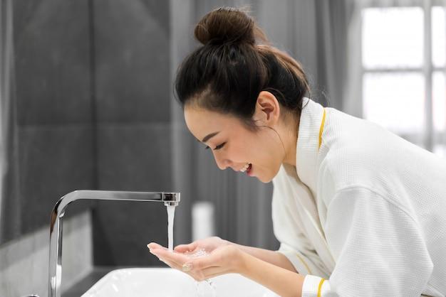 Piękna młoda asiann kobieta myje czystą twarz wodą i uśmiecha się przed lustrem w łazience. piękno i spa. idealna świeża skóra
