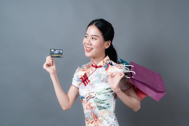 Piękna młoda azjatka nosi chińską tradycyjną sukienkę z torbą na zakupy i kartą kredytową