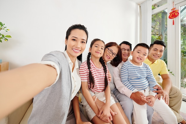Piękna młoda azjatka robi selfie z rodzicami, mężem i dziećmi, gdy są zebrani w domu