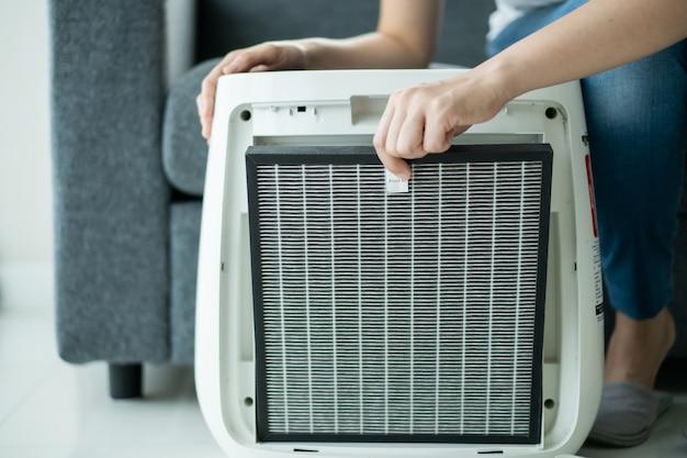 Piękna młoda azjatka trzymająca węglowy filtr oczyszczacza powietrza hepa w salonie, kobieta przygotowuje filtr oczyszczacza powietrza, który ma zastąpić stary. koncepcja opieki zdrowotnej i dobrego stylu życia.