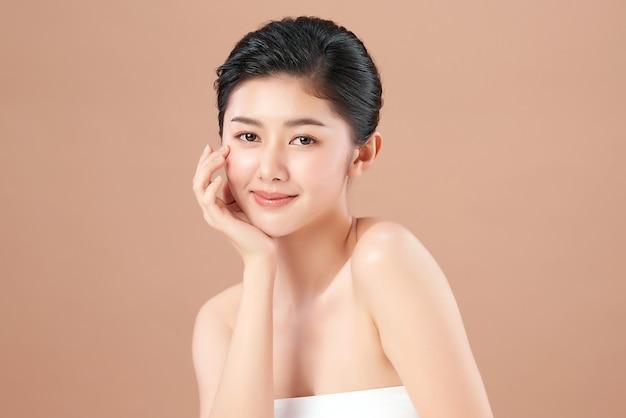 Piękna młoda azjatka z czystą, świeżą skórą na beżowej ścianie, pielęgnacja twarzy, zabieg na twarz, kosmetologia, uroda i spa, portret azjatyckich kobiet.
