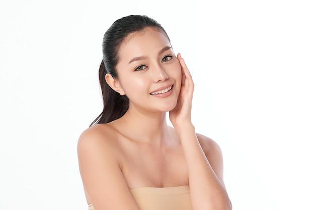 Piękna młoda azjatka z czystą, świeżą skórą na białej ścianie, pielęgnacja twarzy, zabieg na twarz, kosmetologia, uroda i spa, portret azjatyckich kobiet