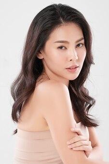 Piękna młoda azjatka z czystą, świeżą skórą na białej ścianie, pielęgnacja twarzy, zabieg na twarz, kosmetologia, uroda i spa, portret azjatyckich kobiet.
