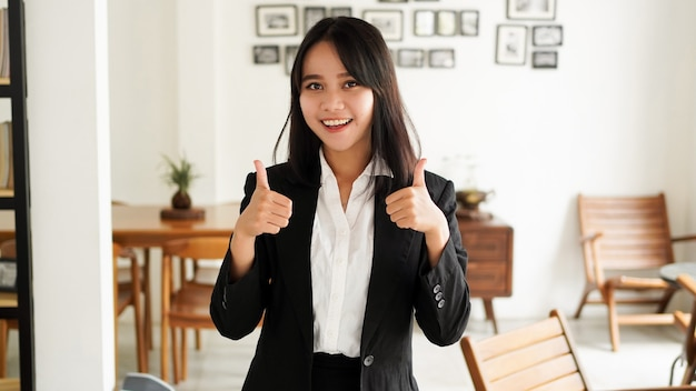 Piękna młoda azjatycka biznesowa kobieta w garniturze i dobrze palcem ręce w biurze