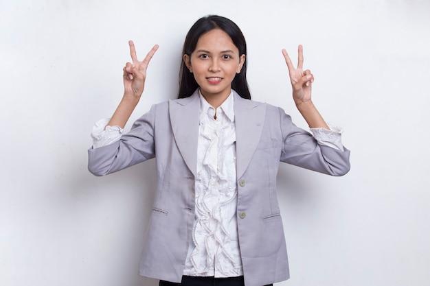 Piękna młoda azjatycka dziewczyna pokazująca gest pokoju lub zwycięstwa na białym tle