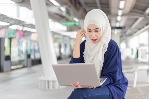 Piękna młoda azjatycka dziewczyna pracuje przy skytrain z laptopem. muzułmanki