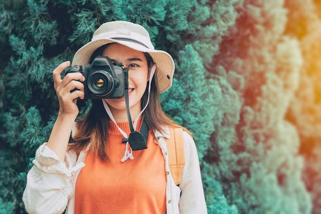 Piękna młoda azjatycka fotografka nastolatka podróżuje z aparatem fotograficznym zrób zdjęcie turysta styl życia stojący uśmiech z kapeluszem