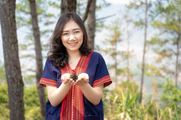 Piękna młoda azjatycka kobieta cieszy się patrzejący pięknych sosna rożki w sosnowego lasu zakończeniu up z kopii przestrzenią.