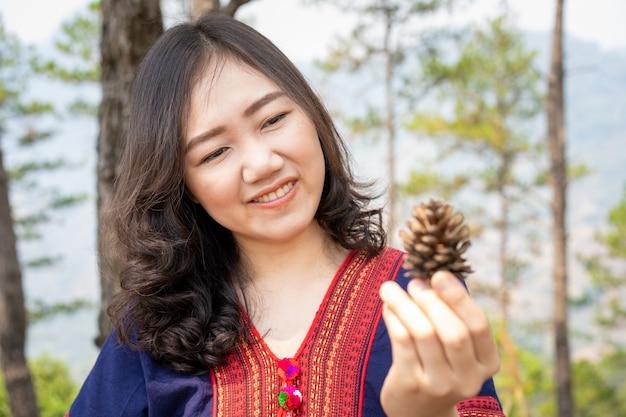 Piękna młoda azjatycka kobieta cieszy się patrzejący pięknych sosnowych rożki w sosnowego lasu zakończeniu up.