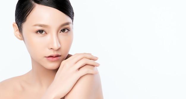Piękna młoda azjatycka kobieta dotyka jej ciało z świeżą zdrową skórą, odizolowywającą na biel ścianie, piękno kosmetykach i twarzy traktowania pojęciu.