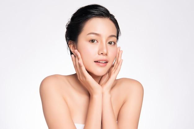 Piękna młoda azjatycka kobieta dotyka jej czystej twarzy świeżą zdrową skórą, odizolowana, kosmetyka i koncepcja zabiegu na twarz,