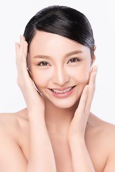 Piękna młoda azjatycka kobieta dotyka jej czystej twarzy świeżą zdrową skórą, odizolowywającą na białej ścianie, kosmetyka piękno i koncepcja leczenia twarzy