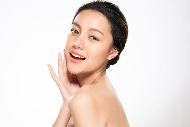 Piękna młoda azjatycka kobieta dotyka miękkiego policzek i uśmiech z czystą i świeżą skórą. szczęście i radość, na białym tle, piękno i kosmetyki,