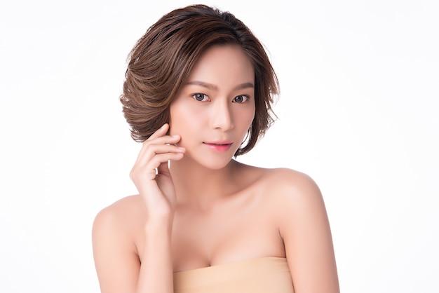 Piękna młoda azjatycka kobieta dotyka miękkiego policzek i uśmiech z czystą i świeżą skórą