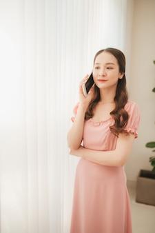 Piękna młoda azjatycka kobieta dzwoni i rozmawia z rodziną za pomocą telefonu komórkowego