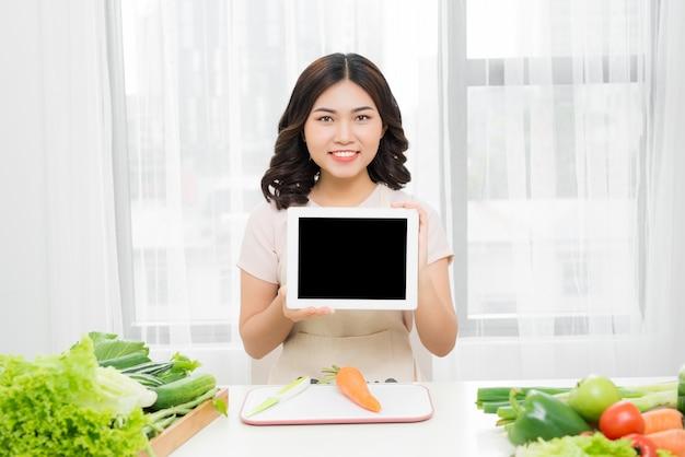 Piękna młoda azjatycka kobieta, która pokazuje ekran komputera typu tablet
