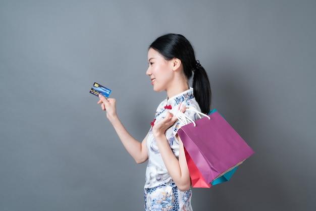 Piękna młoda azjatycka kobieta nosi chińską tradycyjną sukienkę z torbą na zakupy i kartą kredytową na szarym tle