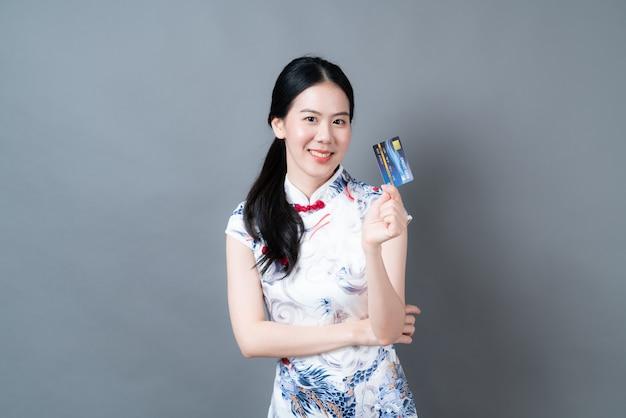 Piękna młoda azjatycka kobieta nosi chiński tradycyjny strój z ręką trzymającą kartę kredytową