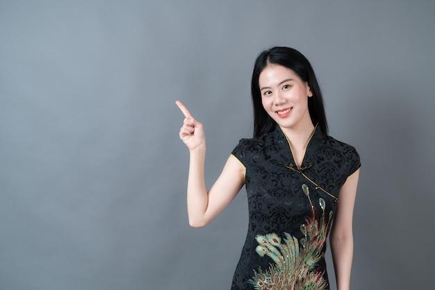 Piękna młoda azjatycka kobieta nosi czarną chińską tradycyjną sukienkę z ręką prezentującą się na boku